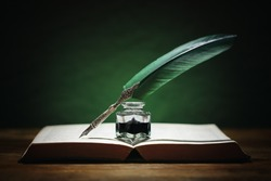 Quill pen and inkwell resting on an old book with green background concept for literature, writing, author and history