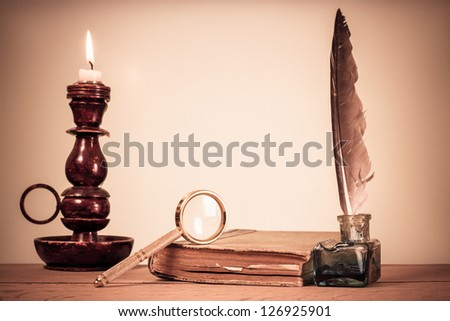 Quill pen, inkwell, book, magnifying glass and candle on the table
