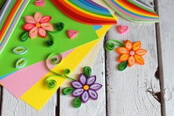 Quilling technique. Paper strips, flowers, scissors, elements. Handmade crafts on holiday theme: Birthday, Mother's Day, March 8, Wedding. Making decoration or greeting card. Children's DIY concept.