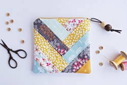 Quilted patchwork notions bag, buttons and retro scissors on white