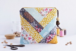 Quilted patchwork notions bag, glass jar with buttons, retro scissors and vintage wooden spools on white
