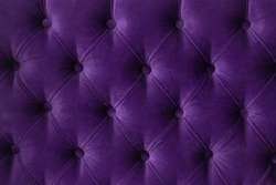 Quilted velour buttoned purple violet color fabric wall pattern background. Elegant vintage luxury sofa upholstery. Interior plush backdrop