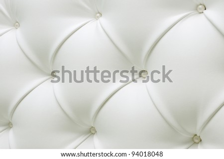 Quilted white leather with white pearls. Leather upholstery. White leather with pearl buttons. Background of expensive furniture. The texture of quilted furniture.