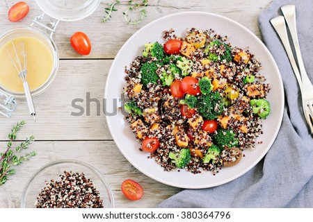 Quinoa salad with broccoli, sweet potatoes and tomatoes on a rustic wooden table. Three-color quinoa salad. Superfood and healthy eating concept.