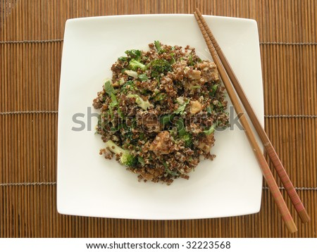 quinoa salad with broccoli, tofu, cilantro, and sesame ginger dressing on a white squared china plate placed on a bamboo matte