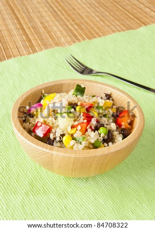 Quinoa salad with colorful vegetables in a wooden bowl