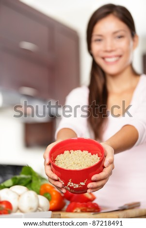 quinoa. Woman showing bowl of cooking quinoa to use for healthy salad. Smiling multiracial female model.