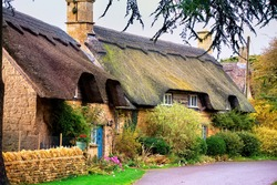 Quintessentially English row of thatched cottages in Gloucestershire England on cloudy fall day. Traditional buildings, thatching is craft of building roof with dry vegetation like straw or water reed