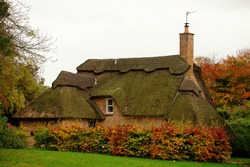 Quintessentially English thatched cottage in Gloucestershire England on a cloudy fall day. Traditional building, thatching is the craft of building a roof with dry vegetation like straw or water reed.