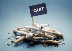 Quit or stop smoking concept pile of damaged cigarettes with sign