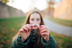 Quit Smoking. Closeup Of Beautiful Girl Holding Broken Cigarette In Hands. Portrait Of Smiling Young Woman Breaking Cigarette In Half, Quitting To Smoke Cigarettes.
