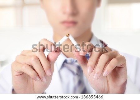 Quit smoking, doctor hands breaking the cigarette, close up, asian model