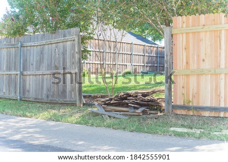 Quite back alley with wooden fence replacement in progress at residential neighborhood near Dallas, Texas, America. Pile of rotted panels near new lumber boards fence installation remodel Photo stock ©
