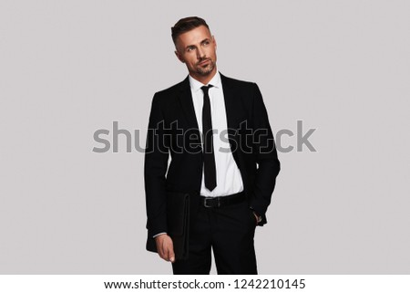 Quite contemplation. Thoughtful young man in full suit keeping hand in pocket and looking away while standing against grey background