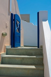 Quite street with three steps and old blue door on island of Santorini in Fira, Greece.