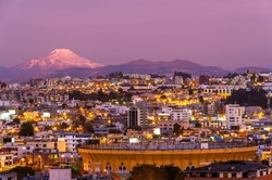 Quito city at night in modern district with the Cayambe volcano and bullfighting arena, Ecuador.