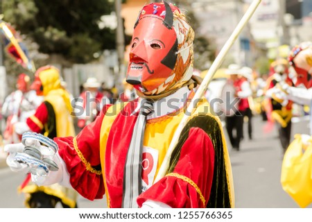 Quito, Ecuador - September, 03, 2018: Portrait view of man wearing a mask and dressed up as devil in the diablada, during a celebration of diablada #1255766365