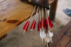 Quiver with wooden arrows lying on the table. White and red plumage