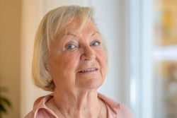 Quizzical senior lady glancing sideways at the camera as she stands near a large window at home in a close up head shot