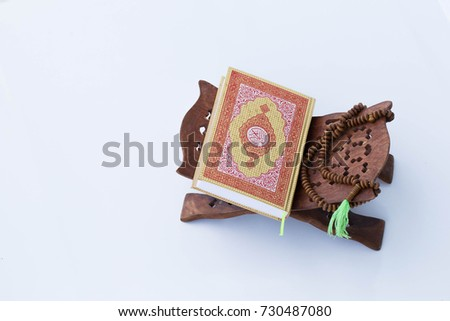 Quran - holy book of Muslims around the world, placed on a wooden board with a white background. #730487080