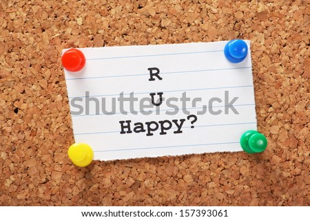 R U Happy typed onto a piece of lined paper and pinned to a cork notice board. We look for happiness in our relationships,work and our daily lives.