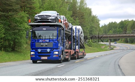 RAASEPORI, FINLAND - MAY 31, 2014: MAN car carrier hauls a load of new cars. The Finnish automotive industry estimates that a total of 109,000 new passenger cars will be sold in Finland in 2015.