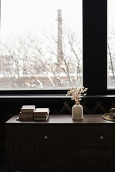 Rabbit bunny tail grass bouquet, books stack on solid wooden table against window. Aesthetic dark home interior design concept. Beautiful floral foliage composition.