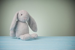 Rabbit doll with big ears isolated on blue wooden table with copy space. Cute doll bunny animal and fluffy fur for kids, baby.