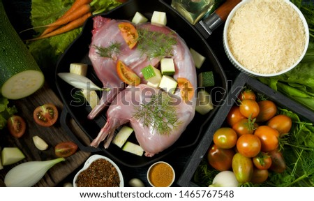 Rabbit meat. A whole carcass of a young, fresh rabbit. rabbit on a wooden table with vegetables and spices. View from above. Copy space. #1465767548