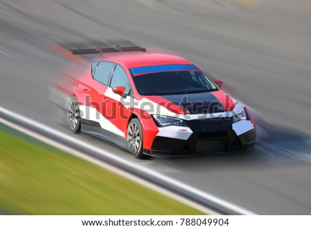 Race car racing at high speed on speed track with motion blur at sunny day on a racing track