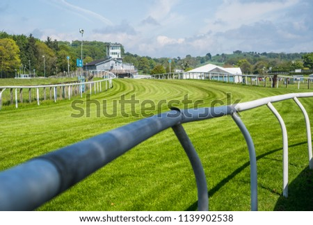 Race course for horses showing the boundary railings and club house in the distance. Taken on a bright sunny day. Stock photo ©