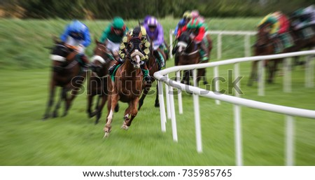 Race horses and jockeys racing fast around the turn of the track with motion blur effect  #735985765
