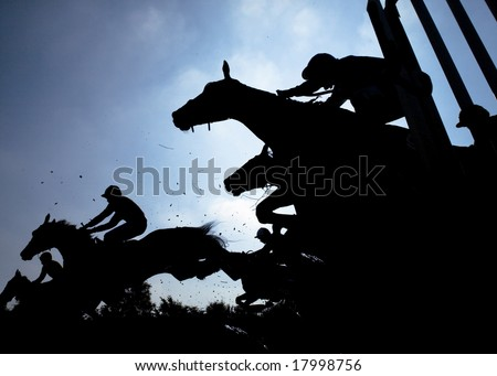 race horses jumping over a hurdle at speed photographed in silhouette