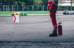 Race marshall stand guard of the safety crew ready to rescue in case of accident during a racing car.