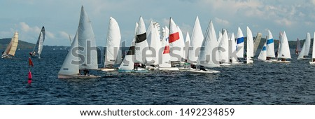 Race Start. Children sailing in small colourful boats and dinghies in Australian high school championships. Teamwork by junior sailors racing on Lake Macquarie. Photo for commercial use.