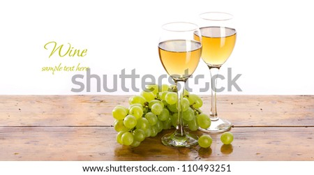 racemation and two wineglass with yellowish liquid on wooden table, on white background #110493251