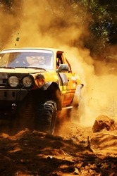 Racer at terrain racing car competition, the car try to cross extreme off road with red earth,  wheel make splash of soil and dusty air, competitor  adventure in championship spirit