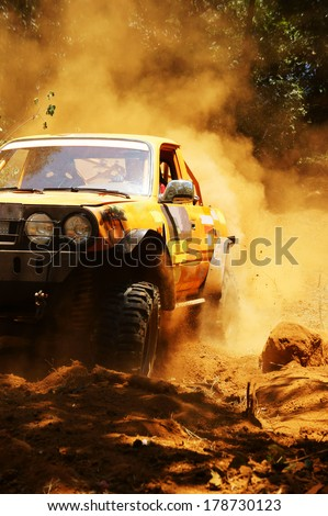 Racer at terrain racing car competition, the car try to cross extreme off road with red earth,  wheel make splash of soil and dusty air, competitor  adventure in championship spirit  #178730123