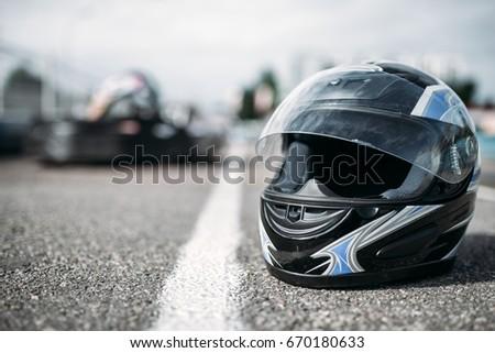 Racer helmet on asphalt, karting sport concept #670180633