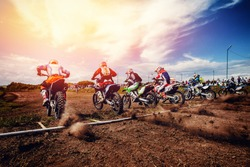 Racer on motorcycle participates in motocross prepare for start against team of rivals. Concept active extreme rest. ray of light sunset.