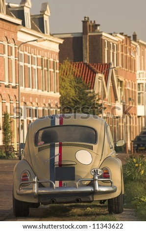 Racing car (Beetle) parked at the edge of a set of row houses