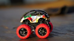 Racing car on the floor. Car toy with big wheels and to play in childhood. Beautiful car toys closeup.