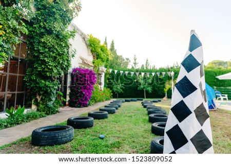 Racing circuit with tires in a patiotrasero for children to play at races, with a checkered flag.