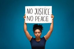 Racism protest demonstration. Black woman striking with placard No Justice No Peace, blue studio background