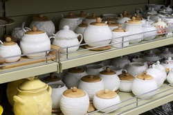 Rack of ceramic dishes in a home goods store. White ceramic pots with wooden lids, sugar bowls, containers for bulk products. Tableware sale. Selective focus