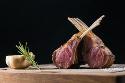 Rack of freshly grilled new zealand organic lamb cooked medium rare and put on a wooden plate and shot by professional food photographer