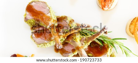 Rack of lamb cut into individual cutlets topped with a sprig of fresh rosemary and served drizzled with gravy for a gourmet dinner