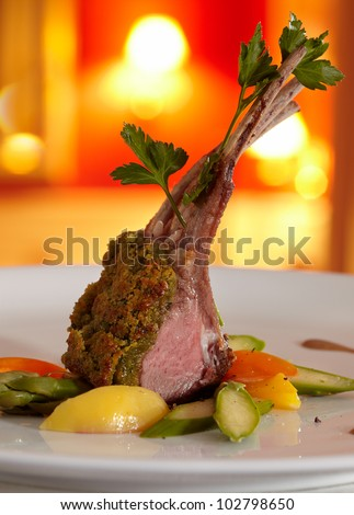 Rack of lamb in a herb crust, served with ratatouille and Port wine-sauce. Close-up. In the background a restaurant in red colours, blurred.
