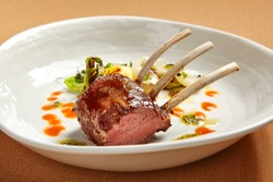 Rack of lamb in white deep plate close-up. Luxury restaurant main course side view. Fancy dish closeup. Mutton ribs. Meat piece served in bowl. Roasted meat with vegetable garnish. Culinary art
