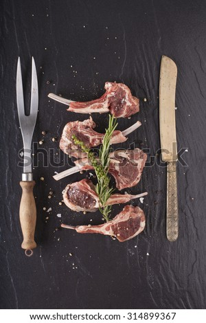 Rack of lamb, Raw rack of lamb cut in pieces decorate and seasoning with rosemary tomato herbs and olive oil fork and knife on black stone